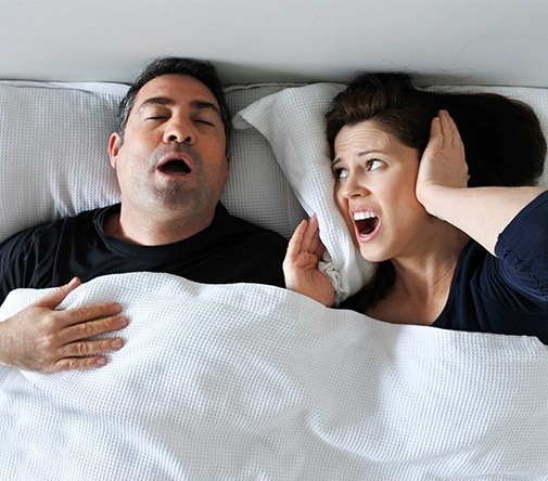 man snoring while wife covers ears