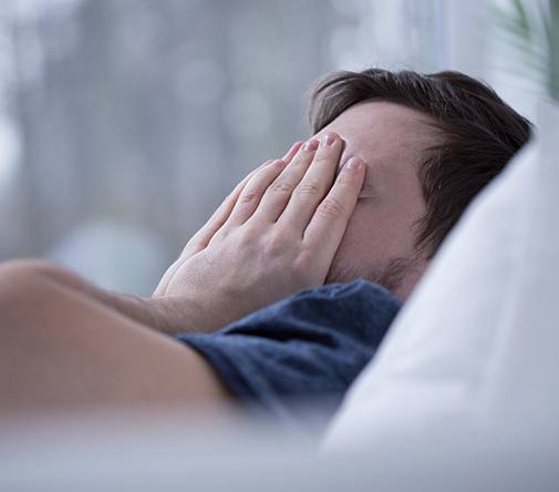 man covering face in bed