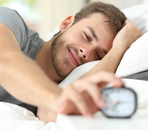 man smiling while turning off alarm clock