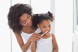 parent teaching their child how to brush their teeth