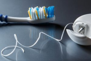 Toothbrush and dental floss sitting on a gray surface