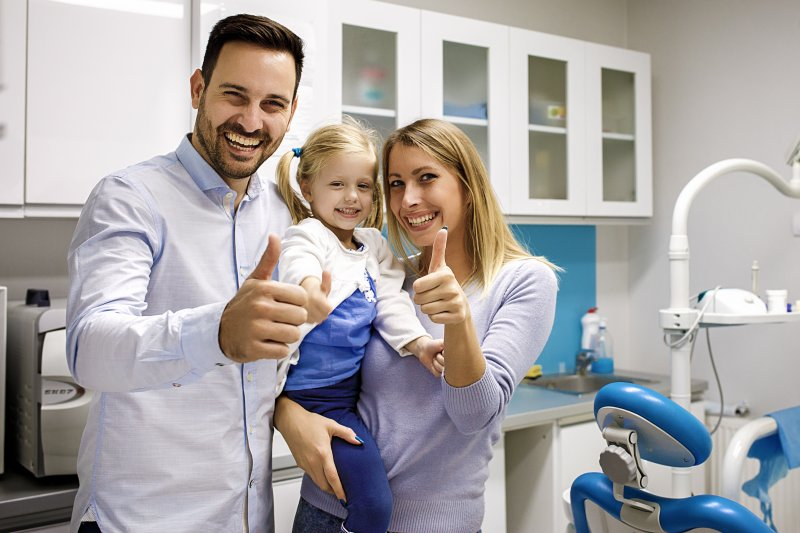 Family giving thumbs up after their dental checkup