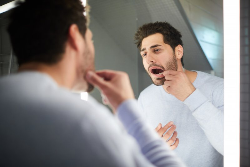 Man checking his teeth in a mirror