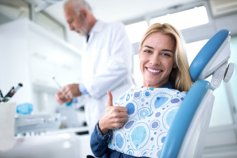 Woman smiling and giving thumbs up during appointment