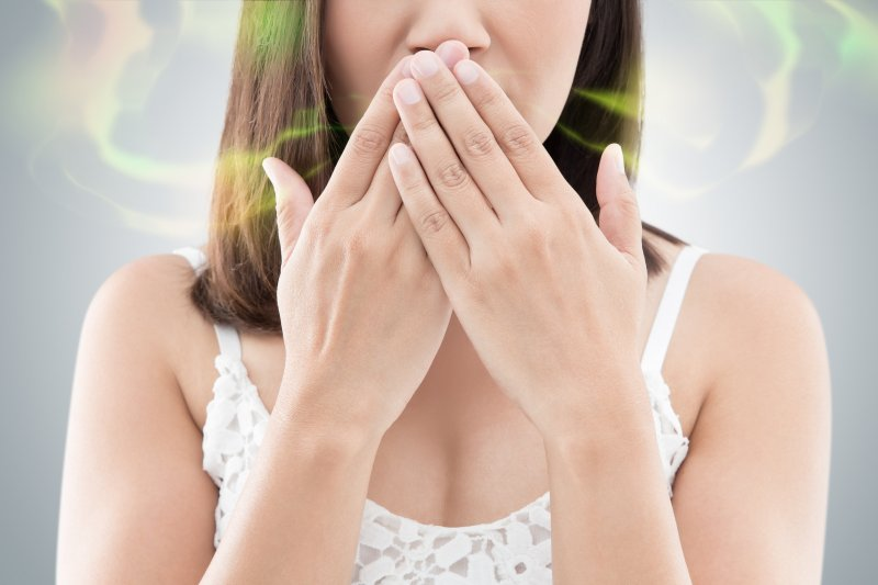 Woman covering her mouth to hide bad breath