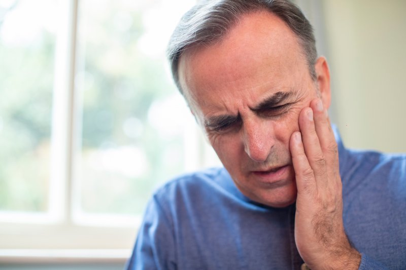 an older man wearing a blue shirt and holding his cheek in pain because of a dental emergency