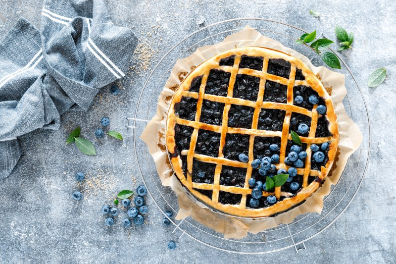a beautiful blueberry pie inside a pie plate and sitting on a table