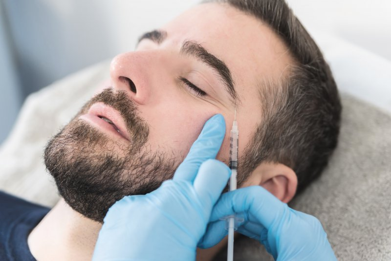 Male patient getting BOTOX injections around his eye