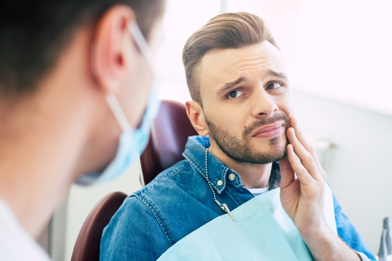 Man talking to dentist about tooth pain