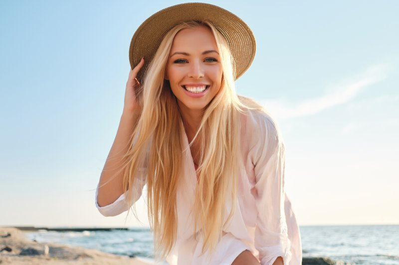 girl with cosmetic treatment smiling on beach
