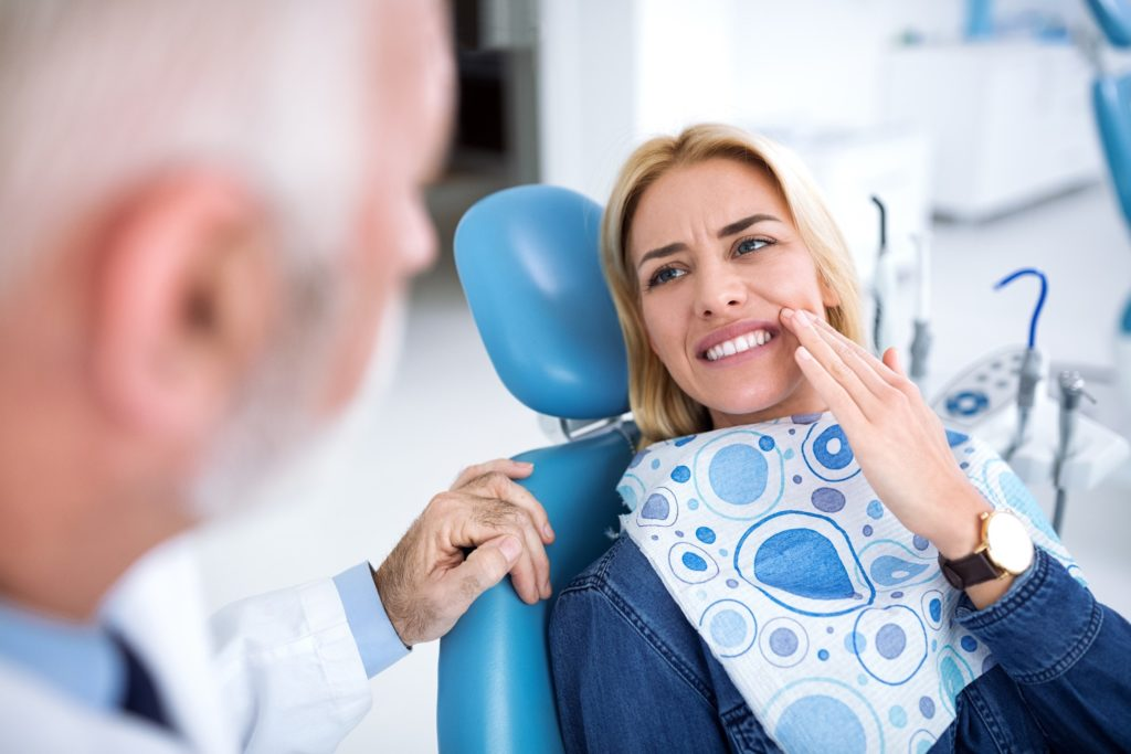 Woman with cracked tooth talking to dentist